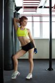 Lovely muscular woman posing with punching bag — Stock Photo