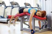 Tired sportswoman lying on sports bench — Stock Photo