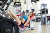 Cheerful young sportswoman exercising in gym — Stock Photo
