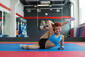 Smiling sportswoman doing stretching exercises — Stock Photo