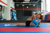 Funny sportswoman stretches at camera in gym — Stock fotografie