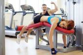Merry man and woman tired of training in gym — Stock Photo