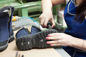 Image of worker processing demi-season boots — Stock Photo