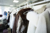 Clean clothes hanging on hangers at dry cleaners — Stockfoto