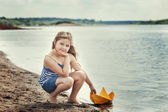 Cute girl posing with homemade paper boat by lake — Zdjęcie stockowe