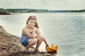 Cute girl posing with homemade paper boat by lake — Stockfoto