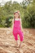 Cute little model posing in pink overall at beach — Stock Photo