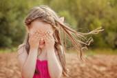 Cute little girl playing hide and seek with camera — Stock Photo