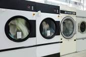 Running washing machines in laundry room — Stock Photo