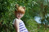Cute red-haired little girl posing near tree — Photo