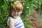Shy red-haired girl posing with tree — ストック写真