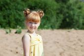 Adorable red-haired girl posing at camera in park — ストック写真