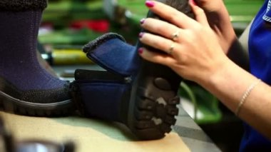 Manufacture of footwear. Worker aligns boots sole — Vídeo stock