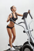 Sexy young sportswoman exercising on simulator — Stock Photo