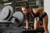 Exciting brunette exercising with dumbbells in gym — Stock Photo