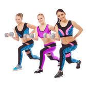 Smiling female athletes posing with dumbbells — Stock Photo