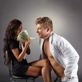 Sexy girl attracts dancer with pack of dollars — Stock Photo