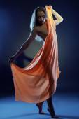 Nude girl dancing with cloth in ultraviolet light — Stock Photo
