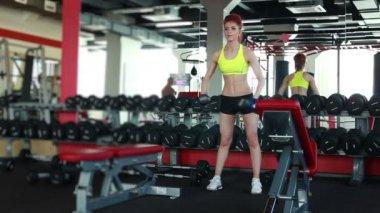 Štíhlá dívka trénink s činkami v tělocvičně — Stock video
