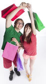 Happy Couple Holding and Raising Paper Bags — Stock Photo