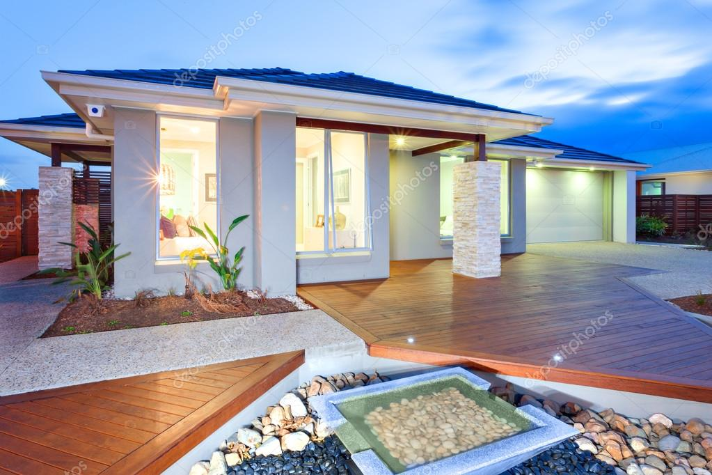 villa moderna con pavimento in legno e cortile in cemento