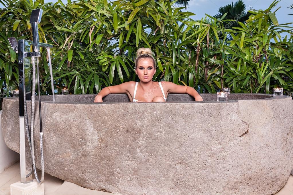 Giovane brunetta con un bikini bianco in una vasca di pietra ...