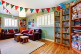 Room with bookcase decorated with colorful flags — Stock Photo