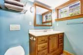 Blue bathroom interior with wooden vanity cabinet — Stockfoto