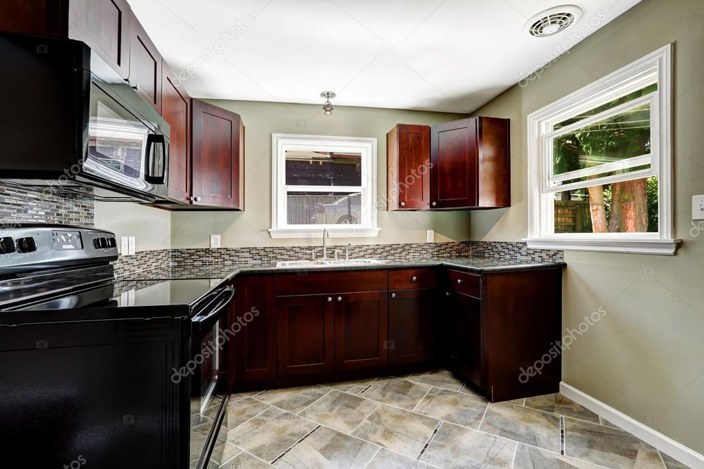 Kitchen with bright burgundy cabinets and black appliances for Burgundy kitchen cabinets pictures
