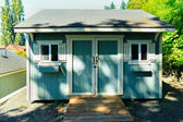 Wooden shed with white trim — Stock Photo