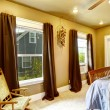 Warm tones bedroom with brown curtains — Stock Photo