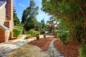 Backyard garden with dry grass and concrete tile walkway — Stock Photo