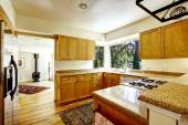 Simple kitchen interior with wooden cabinets and granite tops — Stock Photo