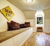 Lavička s koberci kryt a hnědé polštáře v prázdné místnosti — Stock fotografie
