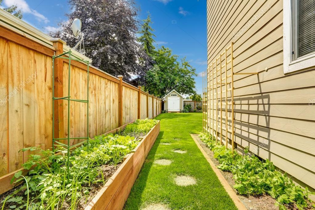 fenced backyard with garden bed stock photo iriana88w