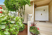 Neat entrance porch with white door and flower pot on stairs — Stock Photo