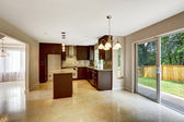 Modern kitchen room with matte brown cabinets and exit to backya — Stock Photo