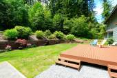 House with wooden patio area overlooking backyard landscape — Stock Photo