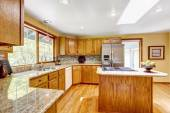 Golden tones kitchen interior with island and skylight — Stock Photo