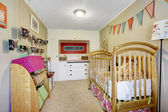 Baby room interior with wooden crib — Stock Photo