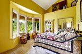 Luxury bedroom in bright yellow color — Stock Photo