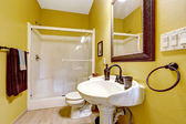 Bright yellow bathroom with glass door shower — Stock Photo