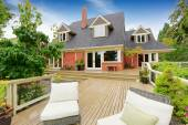 Brick house with walkout deck. Patio area with wicker chairs — Stock Photo