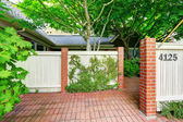 Wooden fence with brick columns and tile floor front yard — Stock Photo