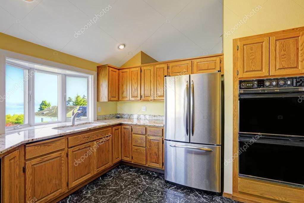 Cocina comedor con encimeras de granito y piso de azulejo negro ...