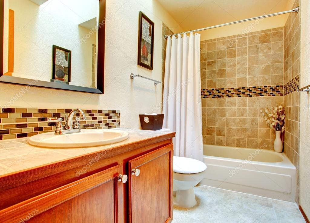 Interior de cuarto de ba o con pared de azulejo beige for Cuartos de bano beige