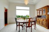 Bright dining room with carved wood cabinet — Stock Photo