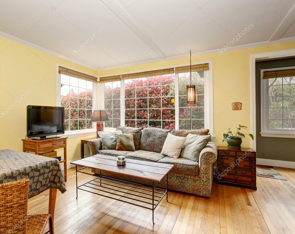 Härlig lövträ vardagsrum med färgglad soffa och gula väggar ...