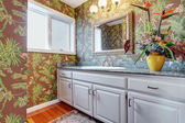 Coloful bathroom with floral walls and white hints. — Stock Photo