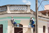 Men painting a facade of a colonial house. — Stockfoto